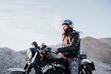 Bearded Man With Dreadlocks Sitting On Motorbike Smoking Electronic Cigarette