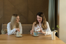 Two Stylish Female Friends With Cups Of Fresh Coffee Smiling And Talking While Sitting At Table In Cozy Restaurant