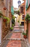 Fototapeta Perspektywa 3d - Menton. Old narrow street in the historic part of the city.