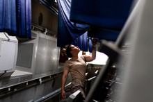 Attractive Female Soldier Looking Up While Standing Inside Modern Military Transport