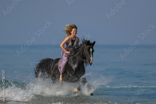 Photo  Portrait of a beautiful blond girl galloping on horseback, dissecting waves on t
