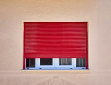 Half Open Red Rolling Shutters Window On Light Ocher Wall