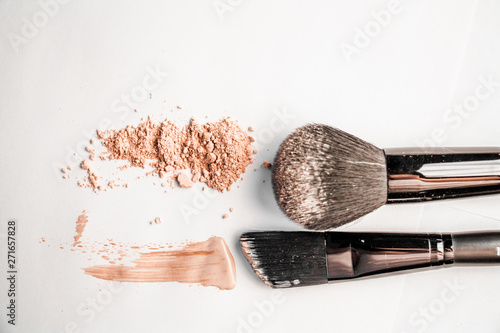 Fotomural  powder slide, a touch of foundation and two black makeup brushes