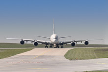 Front View Of A Four Engine Big Jet Plane Waiting On A Taxiway For Taking Off Permission.