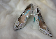 Overhead View Of Tiara Sitting On Top Of A Pair Of Silver Sequined Bridal Shoes On Top Of A Clean White Fur Carpet