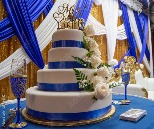 Royal Blue And White Multi Tiered Wedding Cake On A Blue Covered Table Against A Blue White And Gold Ribboned Backdrop Buy This Stock Photo And Explore Similar Images At Adobe