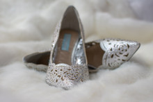 A Pair Of Silver Sequined High Heeled Bridal Shoes Against A Clean White Fur Background Waiting To Be Worn On The Wedding Day