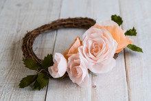 High Angle Close Up Of A Small Wreath With Pale And Salmon Pink Paper Roses.