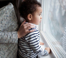 Side View Of Mother And Son Looking Through Window At Home