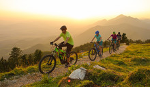 SUN FLARE Cheerful Tourists Ride Electric Bicycles Up A Mountain Trail At Sunset