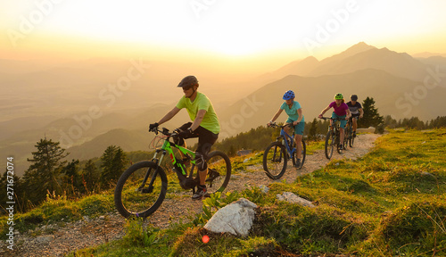 Fototapeta SUN FLARE Cheerful tourists ride electric bicycles up a mountain trail at sunset obraz