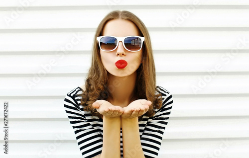 Fotografiet  Portrait close-up woman blowing red lips sending sweet air kiss on white wall ba