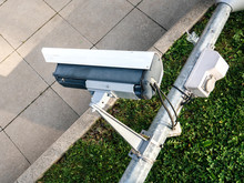 View From Above Of Damaged Surveillance Camera On Street Lamp Pole On The Ground - Vandalism Act On French Street Near Public Parliament Building