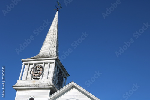 Old weathered wooden white New England church with steeple and clock