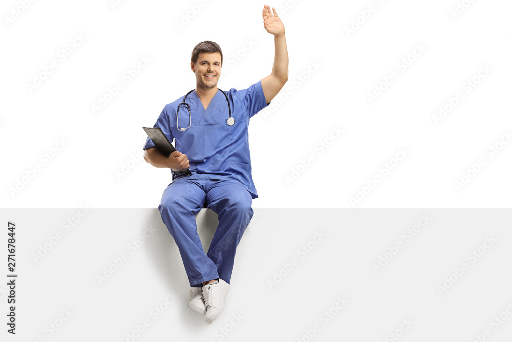 Fototapety, obrazy: Young male doctor in a blue uniform sitting on a white panel and greeting with hand