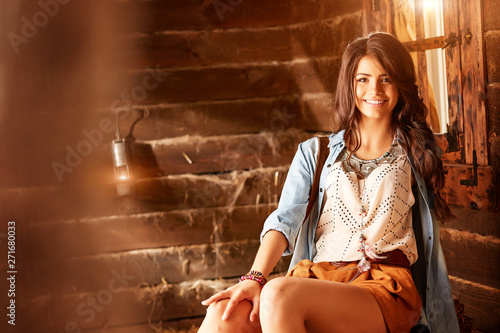 Valokuva  Charming woman with beautiful smile in short shorts and a blue shirt posing in a