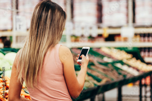 Foto  Woman using mobile phone while shopping in supermarket