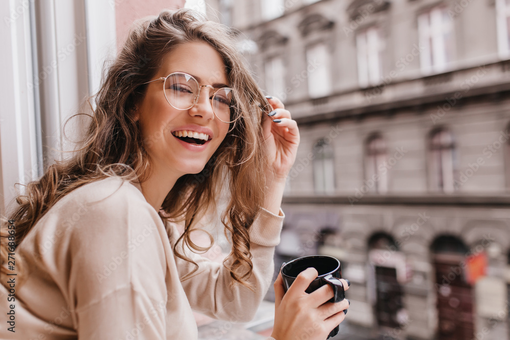 Fototapety, obrazy: Close-up portrait of laughing brunette girl in beige sweater drinking coffee on city background. Lovable lady standing near window and looking at beautiful building with cup of tea.