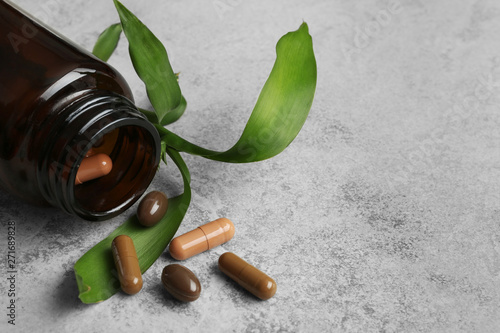 Fotografia  Bottle with vitamin capsules and green leaves on table, space for text