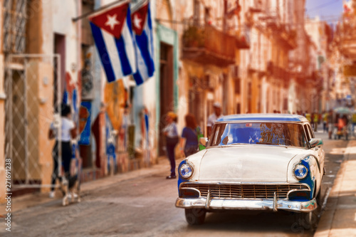 Photo  Cuban flags,old car and  decaying buildings in Havana