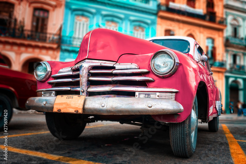 Poster Havana Old car painted hot pink and colorful buildings in Havana