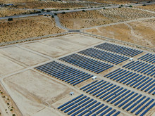 Aerial View Of Genuine Energy Farm In The Hot Arid Desert Of Palm Springs California Features Solar Panels And Wind Turbines To Harness The Power Of Nature To Generate Free Green Energy.