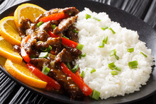 Asian Stir Fry Beef With Bell Pepper In Soybean Orange Sauce Served With Rice Close-up On A Plate. Horizontal
