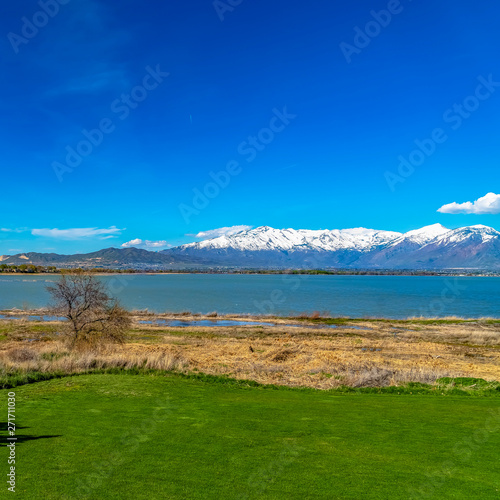 In de dag Golf Square Panorama of a calm lake and mountain with snowy peak under vivid blue sky