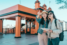 Two Asian Young Girl Friends Standing Outdoor Travel In Graduation Trip On Summer. Beautiful Sisters Backpackers Holding Guide Book Searching Direction Point Front. Angels Flights Railway Station.