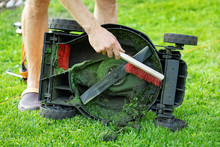 Man With Brush Cleaning Lawnmower From Old Grass