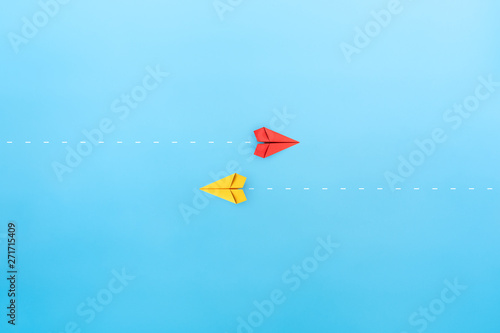 Obraz na plátně  Red and yellow paper planes flying in different directions, blue background