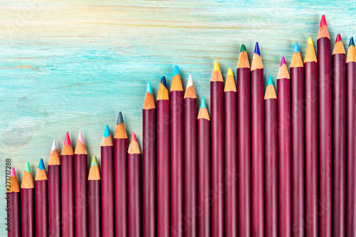 Fototapeta  Many colored pencils forming a growth graph, shot from the top on a teal blue ba