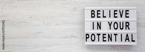 Obraz na plátně  Top view, 'Believe in your potential' words on a lightbox on a white wooden surface