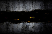 Scary Eyes In Damaged Grungy Crack And Broken Concrete Wall And The Dark Halloween