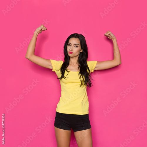 Fotografiet  Strong Beautiful Woman Is Flexing Muscles