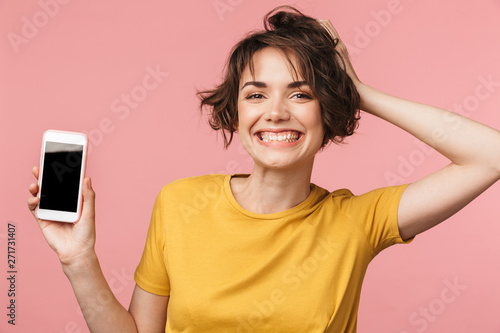 Fotografie, Obraz  Happy young beautiful woman posing isolated over pink wall background using mobile phone