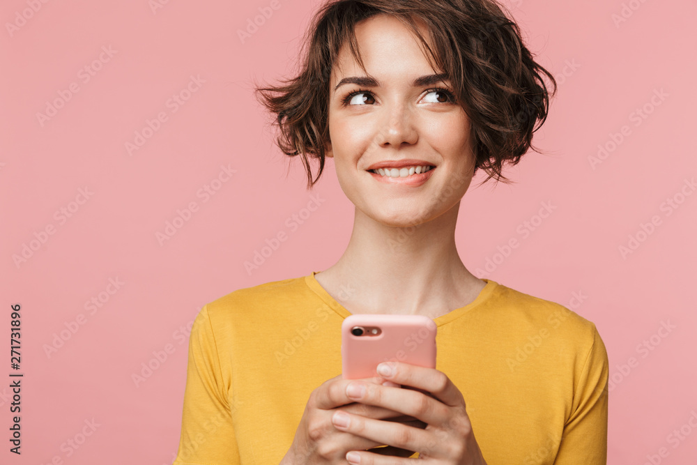 Fototapeta Thinking dreaming young beautiful woman posing isolated over pink wall background using mobile phone.