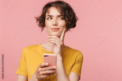 Fotografie, Obraz  Thinking dreaming young beautiful woman posing isolated over pink wall background using mobile phone