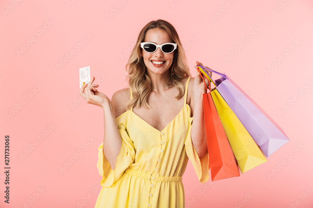 Fototapeta Beautiful happy young blonde woman posing isolated over pink wall background holding shopping bags and credit card.