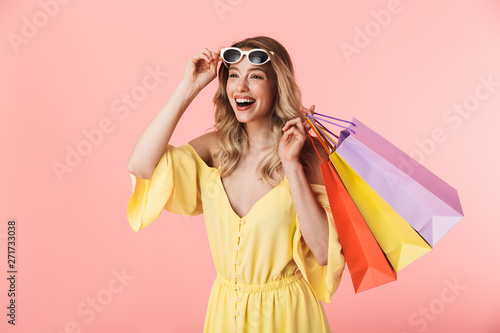Fotomural  Beautiful shocked young blonde woman posing isolated over pink wall background holding shopping bags