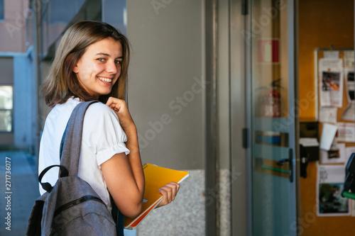 Happy student girl entering school
