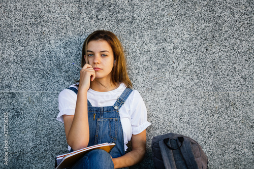Pensive student girl sitting on the floor