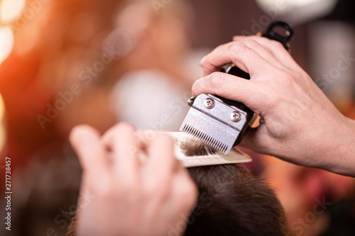Fotografía Close up of a male student having a haircut with hair clippers