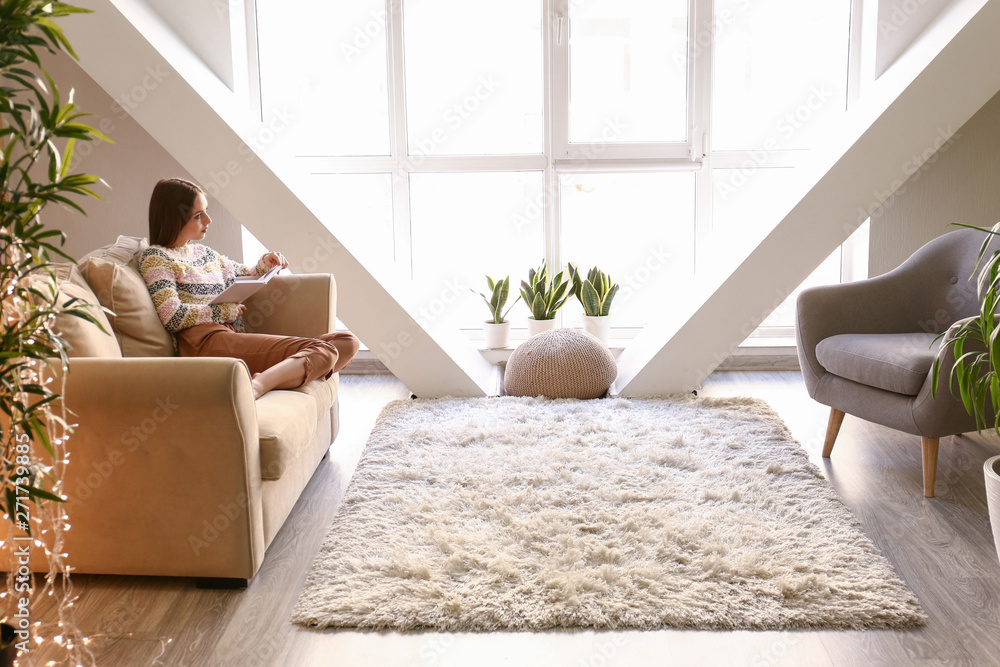 Fototapeta Beautiful young woman reading book at home