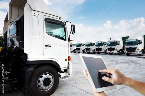 People hand is using tablet multiple photo with new truck fleet is parking on the yard for technology with transportation concept Canvas Print