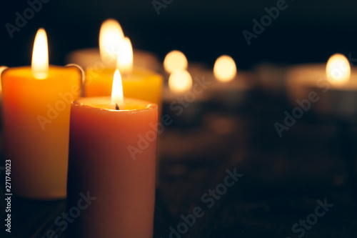 candles burning in darkness over black background Wallpaper Mural