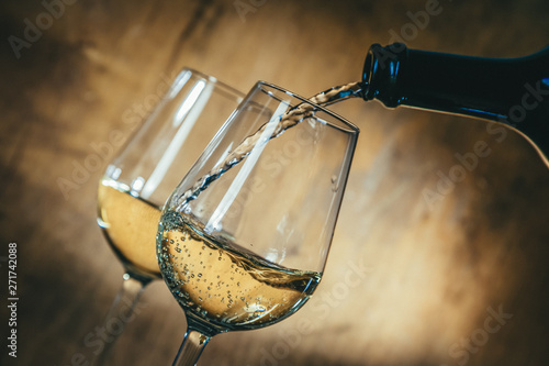 White wine in glasses on rustic background, copy space