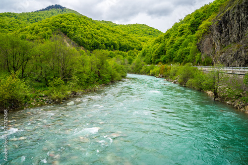 Montenegro, Azure waters of moraca river flowing parallel to the road through green forested moraca canyon nature landscape