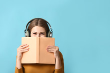 Young Woman Listening To Audiobook On Color Background