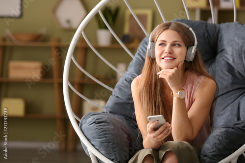 Fotografía  Young woman listening to audiobook at home